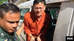 Ny Chakrya, National Election Committee officer, was escorted by the security officers to the appeal court on November 28, 2016, Phnom Penh, Cambodia. (Kann Vicheika/VOA Khmer)