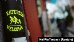 """Almanya'da bazı barlara mültecilerin sokulmadığı haberlerinin ardından Freiburg kentinde kapısının önüne """"Mültecilere açıktır"""" çıkartması yapıştıran bir bar"""