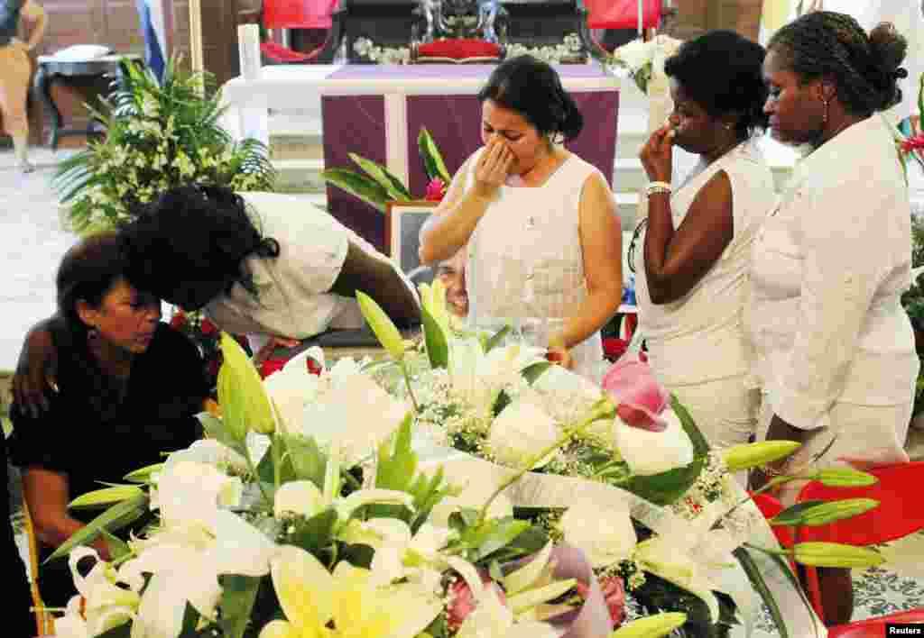 La líder de las Damas de Blanco, Berta Soler, conforta a la viuda de Payá, Ofelia Acevedo, durante el velatorio de los restos mortales del activista pro-derechos humanos.