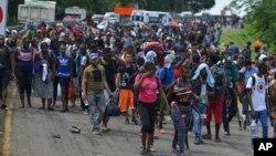 Para migran berjalan di jalan raya Highway 200 menuju Huixtla dekat Tapachula, negara bagian Chiapas, Meksiko, Sabtu, 12 Oktober 2019.