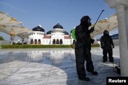 Seorang polisi mengenakan pakaian hazmat menyemprotkan disinfectan di sebuah masjid untuk mencegah penyebaran virus corona (COVID-19) di Banda Aceh, Aceh, 20 Maret 2020. (Foto: Antara via Reuters)