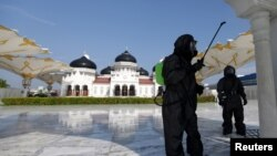 Seorang polisi mengenakan pakaian hazmat menyemprotkan disinfektan di sebuah masjid untuk mencegah penyebaran virus corona (COVID-19) di Banda Aceh, Aceh, 20 Maret 2020. (Foto: Antara via Reuters)