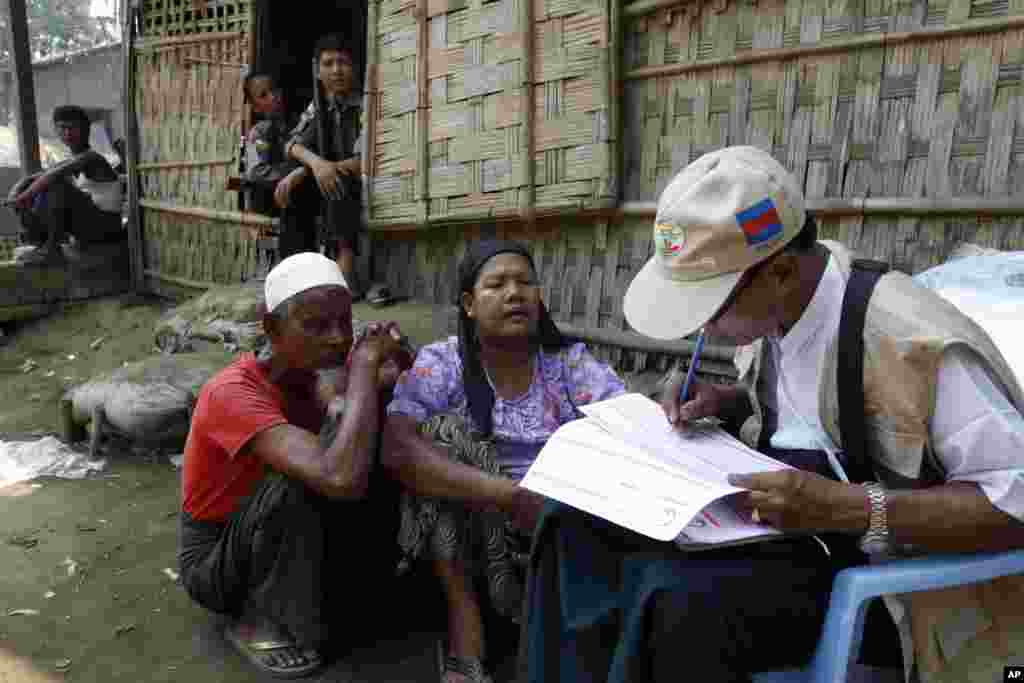 "A census enumerator, right, collects information from a Muslim family as policemen provide security at Thae Chaung village in Sittwe, Rakhine State, western Burma. Enumerators fanned out across the country for a census that has been widely criticized for stoking religious and ethnic tensions, after the government denied members of a long-persecuted Muslim minority the right to identify themselves as ""Rohingya."""
