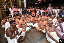Hindu priests and temple staff sit on a protest against a ruling from India's top court to let women of menstruating age entering Sabarimala temple, one of the world's largest Hindu pilgrimage sites, in the southern Indian state of Kerala, Friday, Oct. 19, 2018.