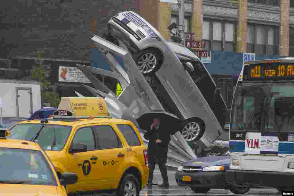 """A man with an umbrella walks past an art installation called """"Climbing Up"""" on the streets of Manhattan, New York. The art installation, which was unveiled on June 6, is inspired by the aluminium body of the 2013 Range Rover."""