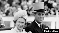 FILE - In this June 19, 1962 file photo, Britain's Queen Elizabeth II and Prince Philip travel by open carriage around the track prior to the race program, at Ascot, England.