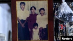 A family photograph of slain journalist Par Gyi, his wife Than Dar, and their daughter posing with Aung San Suu Kyi, is shown at their home in Yangon, Myanmar, Oct. 28, 2014.
