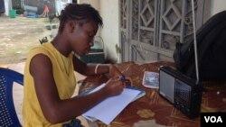 17-year- old Doris Ansumana listening to a radio school program in Freetown, Sierra Leone, October 20, 2014. (N.deVries/VOA).