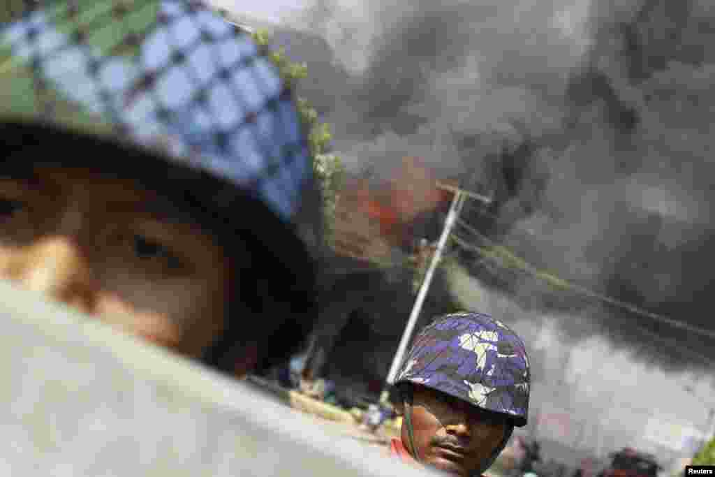Policemen are deployed to provide security amid riots in Meikhtila, Burma. Unrest between Buddhists and Muslims has reduced neighborhoods to ashes and stoked fears that last year's sectarian bloodshed is spreading into the country's heartland in a test of Asia's newest democracy.