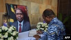 Menteri Pertahanan dan Layanan Nasional Tanzania, Dr Hussein Ali Mwinyi (kanan) menandatangani buku belasungkawa untuk mantan Presiden Benjamin Mkapa di rumahnya di Dar es Salaam, Tanzania, 24 Juli 2020.