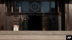 FILE - A paramilitary policeman stands guard at the entrance of China's Supreme Court in Beijing.