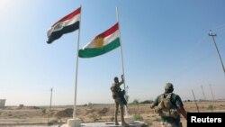 نیروی امنیتی عراق پرچم اقلیم کردستان عراق را بعد از بازپسگیری کرکوک پایین میآورد.