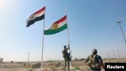 İraq ordusunun əsgəri kürd bayrağını endirir.
