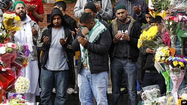 A man reacts during prayers at the scene where three South Asian men were killed by a car during the recent rioting in Birmingham, England, August 11, 2011