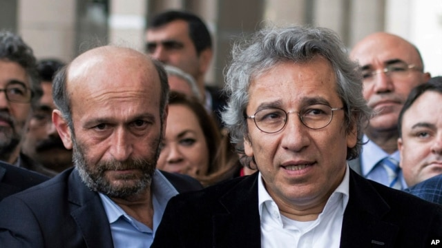 FILE - Can Dundar, right, editor-in-chief of Turkish opposition newspaper Cumhuriyet, and Erdem Gul, the paper's Ankara representative, speak to media outside an Istanbul courthouse, Nov. 26, 2015.
