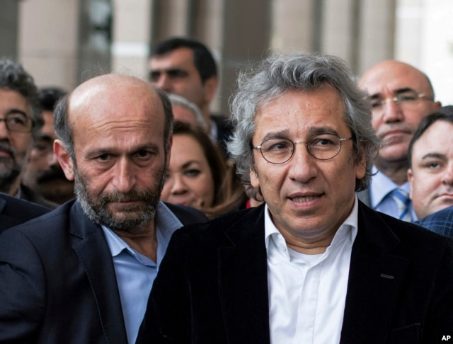 FILE - Can Dundar, right, the editor-in-chief of opposition newspaper Cumhuriyet, and Erdem Gul, left, the paper's Ankara representative, speak to the media outside a courthouse in Istanbul, Turkey, Nov. 26, 2015.