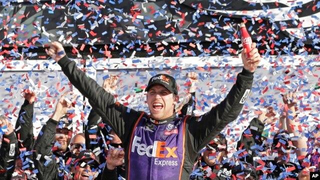 Denny Hamlin celebrates in Victory Lane after winning the NASCAR Daytona 500 Sprint Cup Series auto race at Daytona International Speedway in Daytona Beach, Florida, Sunday, Feb. 21, 2016.