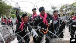 Policija uklanja bodljikavu žicu ispred sedišta policije u Bangkoku, 3. decembar 2013.