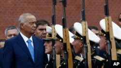 FILE - Uzbek President Islam Karimov (L) watches honor guards passing by during a wreath-laying ceremony at the Tomb of the Unknown Soldier by the Kremlin wall in Moscow, Russia, Apr. 26, 2016.