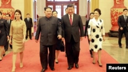 North Korean leader Kim Jong Un and wife Ri Sol Ju, and Chinese President Xi Jinping and wife Peng Liyuan walk together in Beijing, China, in this undated photo released by North Korea's Korean Central News Agency (KCNA) in Pyongyang March 28, 2018.