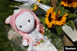 "A child's stuffed toy with the message, ""Thoughts to All the Victims"" is seen as people pay tribute near the scene where a truck ran into a crowd at high speed killing scores and injuring more who were celebrating the Bastille Day national holiday, in Nic"