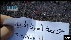 """Một người biểu tình chống chính phủ Syria cầm 1 mảnh giấy ghi dòng chữ """"Ngày Tự do cho các Tù nhân"""", Hama, 15/7/2011"""