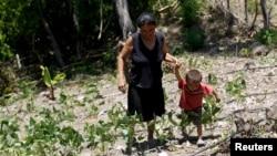 Hình tư liệu - Một người phụ nữ và con trai đi trên mảnh đất bị ảnh hưởng bởi hạn hán ở San Francisco de Coray, Honduras, ngày 13 tháng 8 năm 2015.
