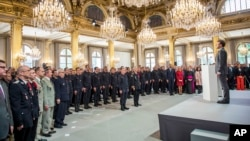 French President Emmanuel Macron stands at attention after addressing Paris Firefighters' brigade and security forces who took part at the fire extinguishing operations of the Notre Dame of Paris Cathedral fire, at the Elysee Palace in Paris, April 18, 2019.