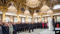 ប្រធានាធិបតីបារាំង Emmanuel Macron ឈរក្រោយពេលថ្លែងទៅកាន់កងកម្លាំងពន្លត់អគ្គិភ័យនិងសន្តិសុខដែលបានចូលរួមក្នុងប្រតិបត្តិការពន្លត់អគ្គិភ័យនៅវិហារ Notre Dame កាលពីថ្ងៃទី១៨ មេសា ២០១៩។