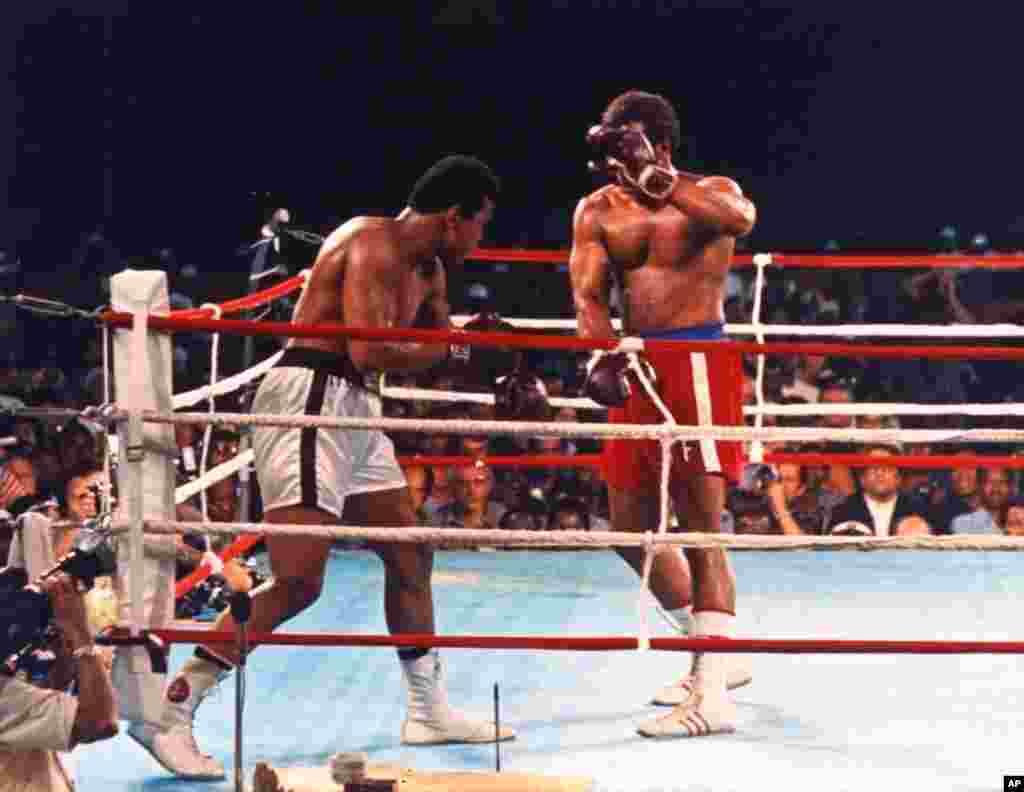 George Foreman, détenteur du titre au moment de la photo, se couvre avec une garde dégarnie, alors que Muhammad Ali décroche un jab (coup sec) au premier round de leur combat pour le titre des poids lourds à Kinshasa, au Zaïre, en Afrique, le 30 Octobre, 1974. Ali a repris le titre avec un KO au huitième round. (AP Photo / stf)