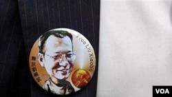 Seorang aktivis pro-demokrasi di Hong Kong mengenakan bros bergambar Liu Xiaobo, pemenang Hadiah Nobel Perdamaian tahun ini yang menjadi tahanan rumah di Beijing.