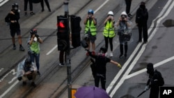 FILE - A protestor smashes a traffic light in Hong Kong, Sunday, Oct. 6, 2019. In Hong Kong, traffic light signals make a special sound so that people who do not see well can safely cross the road.(AP Photo/Vincent Thian)