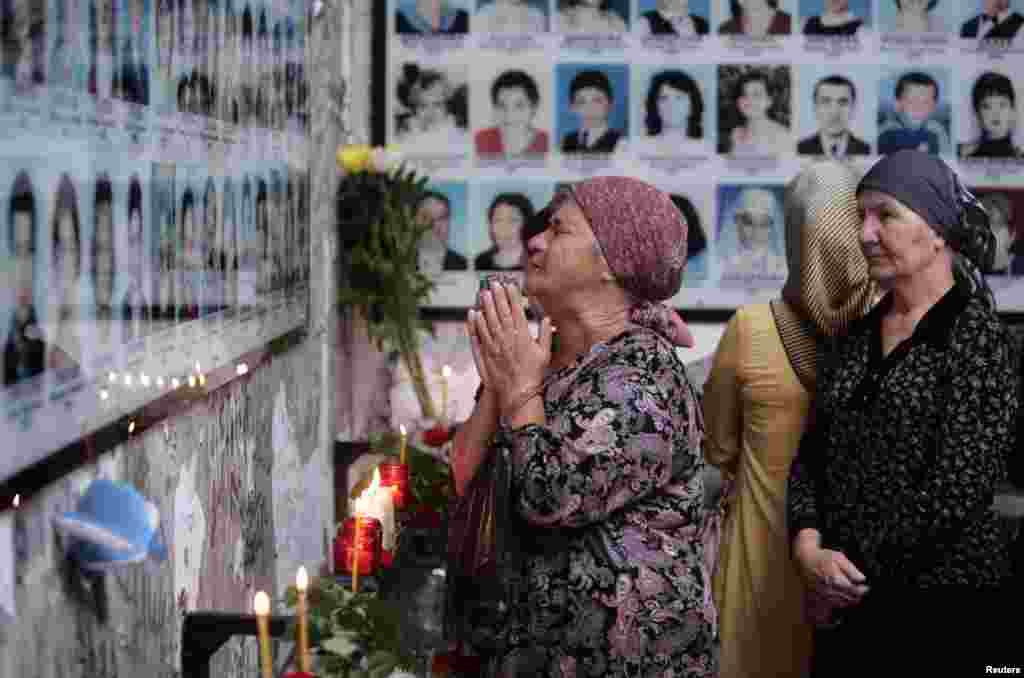 People mourn inside School Number One during a ceremony commemorating the victims of the 2004 hostage crisis in the southern Russian town of Beslan.