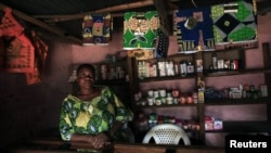 A Congolese woman stands inside her cosmetic shop in Bunagana near the Uganda-Democratic Republic of Congo border, July 9, 2012.