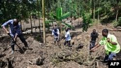 Les volontaires fuient dans les décombres, recherchant des cadavres après le débordement de la rivière Sume dans le village oriental de Wanjenwa, dans le district de Bududa en Ouganda, le 13 octobre 2018.