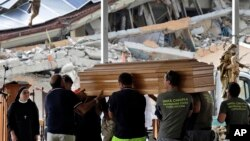 Civil Protection operators carry a casket ahead of a state funeral for some of the victims of last Wednesday's earthquake, in Amatrice, central Italy,