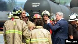 PM Kanada Stephen Harper (kedua dari kanan) mengunjungi lokasi kecelakaan di Lac Megantic, Quebec dan berbicara dengan para petugas pemadam kebakaran (7/7).