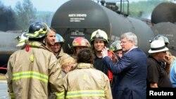 Thủ tướng Canada Stephen Harper nói chuyện với nhân viên cứu hỏa trong khi ông đi thị sát sau khi tai nạn xảy ra, 7/7/13