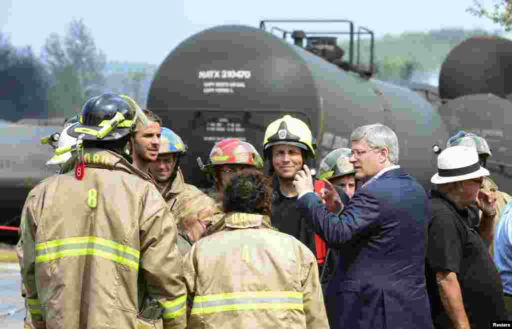 Canada's Prime Minister Stephen Harper speaks with firefighters while he tours the wreckage of the train explosion in Lac Megantic, Quebec, Canada, July 7, 2013.