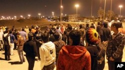 A row of riot police stand between two groups of Bahraini youths in the early hours of Friday in Hamad Town, March 4, 2011