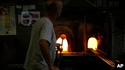 A glass-worker heats glass in a methane powered ovens in a factory in Murano island, Venice, Italy, Oct. 7, 2021.
