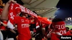 香港球迷在香港隊對巴林隊的國際足球友誼賽上播放中國國歌時用旗子遮住臉發出噓聲。 (2017年11月9日)
