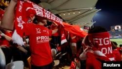 香港球迷在香港队对巴林队的国际足球友谊赛上播放中国国歌时用旗子遮住脸发出嘘声。 (2017年11月9日)