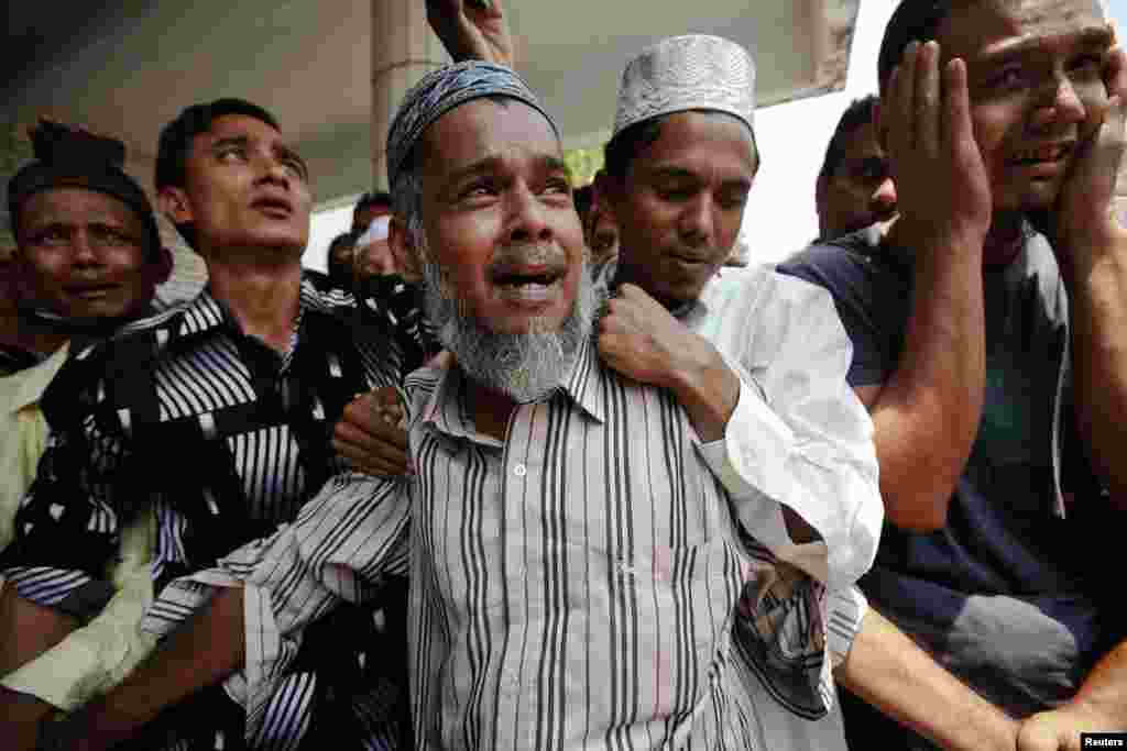 People react as the bodies of victims of a fire are brought for their funeral at Yaeway cemetery in Rangoon, Burma. Thousands of Muslims attended the funeral for the 13 victims of the fire that broke out in a dormitory of an Islamic school in Botataung district of the former capital. The fire caused by faulty electrical equipment, the fire service said.