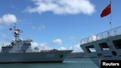 The Chinese People's Liberation Army (PLA) Navy replenishment ship Qiandaohu (866) (L) sails past the PLA Navy hospital ship, Peace Ark, as it docks at the Joint Base Pearl Harbor Hickam to participate in the multi-national military exercise RIMPAC 2014,