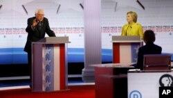 ສະມາຊິກສະພາສູງ Bernie Sanders (ຊ້າຍ) ພວມກ່າວຊີ້ແຈງ ໃນຂະນະທີ່ທ່ານນາງ Hillary Rodham Clinton ຮັບຟັງ ໃນລະຫວ່າງການໂຕ້ວາທີ ຂອງພັກເດໂມແຄຣັດ ທີ່ມະຫາວິທະຍາໄລ ວິສຄັນຊິນ ໃນເມືອງ Milwaukee.