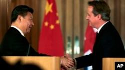 El presidente chino, Xi Jinping (izquierda) estrecha la mano del primer ministro británico, David Cameron durante una conferencia de prensa en Londres, el miércoles 21 de ocutbre de 2015.