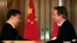 ប្រធានាធិបតីចិន ស៊ី ជិនពីង (ឆ្វេង) ចាប់ដៃជាមួយលោកនាយករដ្ឋមន្ត្រីអង់គ្លេស David Cameron ក្នុងពេលធ្វើសន្និសីទរួមគ្នាមួយ នៅទីក្រុងឡុងដ៍ ប្រទេសអង់គ្លេស កាលពីថ្ងៃទី២១ ខែតុលា ឆ្នាំ២០១៥។
