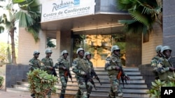 Soldiers from the presidential guard patrol outside the Radisson Blu hotel in Bamako, Mali, in anticipation of the president's visit, Nov. 21, 2015. Islamic extremists armed with guns and grenades stormed the luxury Radisson Blu hotel in Mali's capital Fr