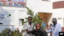 """Watu wakimsaidia msichana aliyejeruhiwa katika shambulio la kujitioa mhanga kwenye mgahawa mashuhuri """"The Village"""". Novemba 3, 2012."""